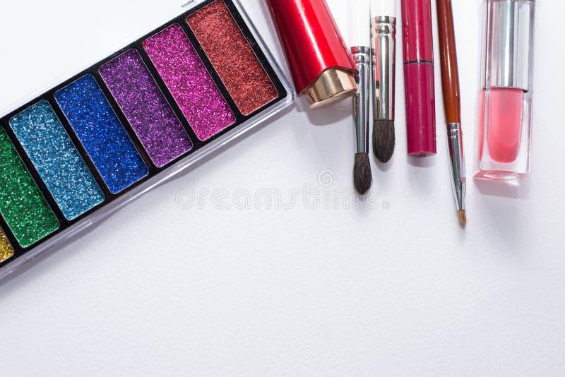 L'immagine posta piana dei cosmetici di bellezza compone con i rossetti, la tavolozza dell'ombretto, le spazzole, lucentezza del  fotografia stock libera da diritti