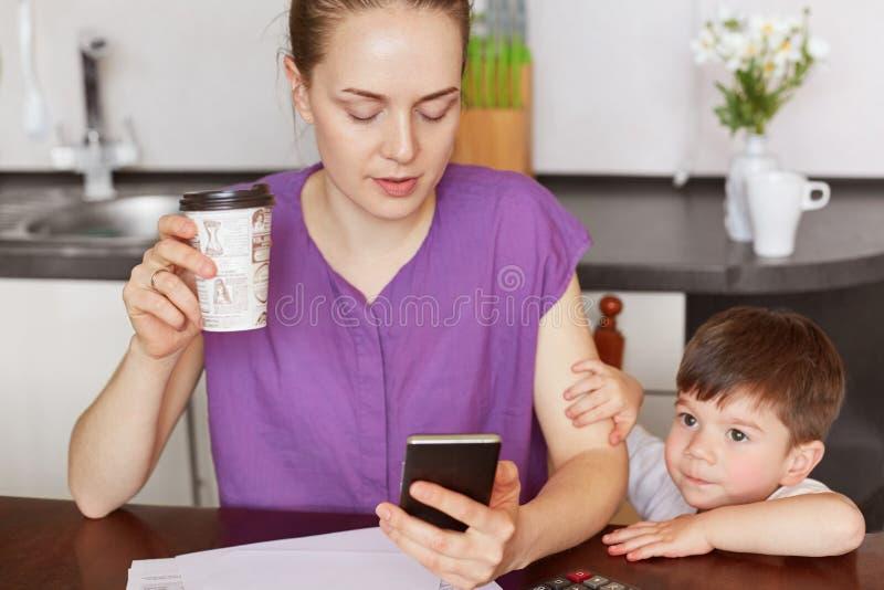 L'immagine potata della lavoratrice concentrata fa il lavoro a distanza, messaggi con l'impiegato sul telefono cellulare, surrond immagine stock