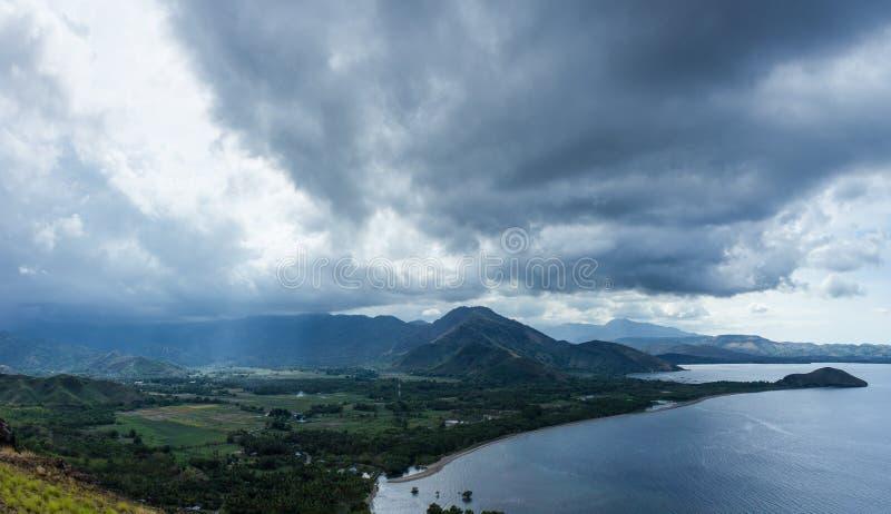 L'immagine scenica del paesaggio di terra e del mare sul villaggio profondo nelle isole del Flores durante il giorno nuvoloso e v immagini stock