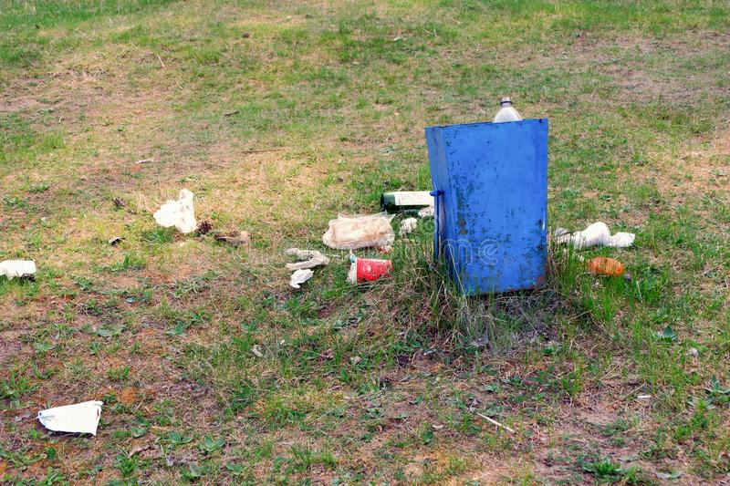L'immondizia è accanto alla pattumiera in un parco fotografie stock