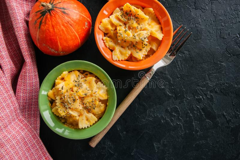 L'imper et le fromage crémeux de potiron ont fait des pâtes cuire au four au-dessus de backg en pierre noir images libres de droits
