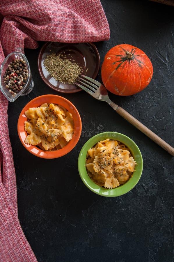 L'imper et le fromage crémeux de potiron ont fait des pâtes cuire au four au-dessus de backg en pierre noir image libre de droits