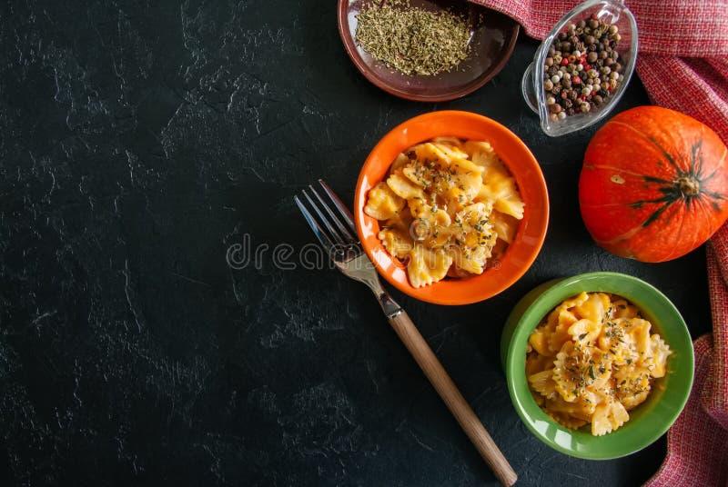 L'imper et le fromage crémeux de potiron ont fait des pâtes cuire au four au-dessus de backg en pierre noir photos libres de droits