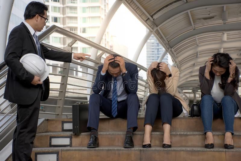 L'impiegato è stato rimproverato dal supervisore che la sensibilità è tenuta seria la sua testa mentre il suo capo sta protestand fotografia stock libera da diritti