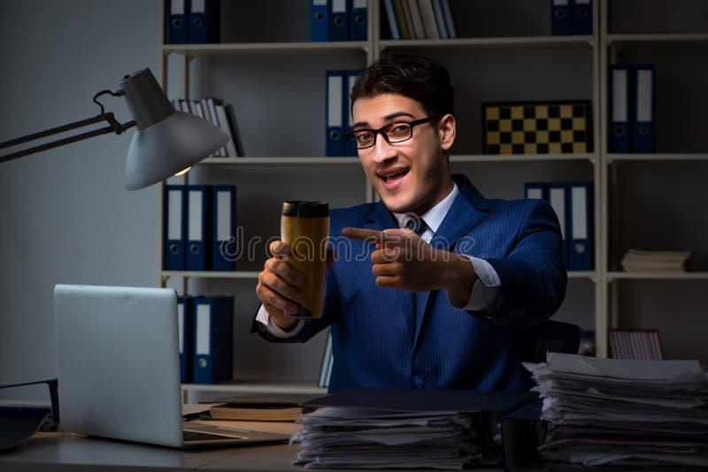 L'impiegato che lavorano tardi e forte caffè bevente per restare sveglio fotografia stock libera da diritti
