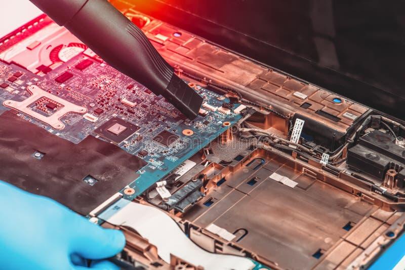 L'impiegato del centro di servizio è impegnato professionale nel liberare il computer portatile dalla polvere immagine stock
