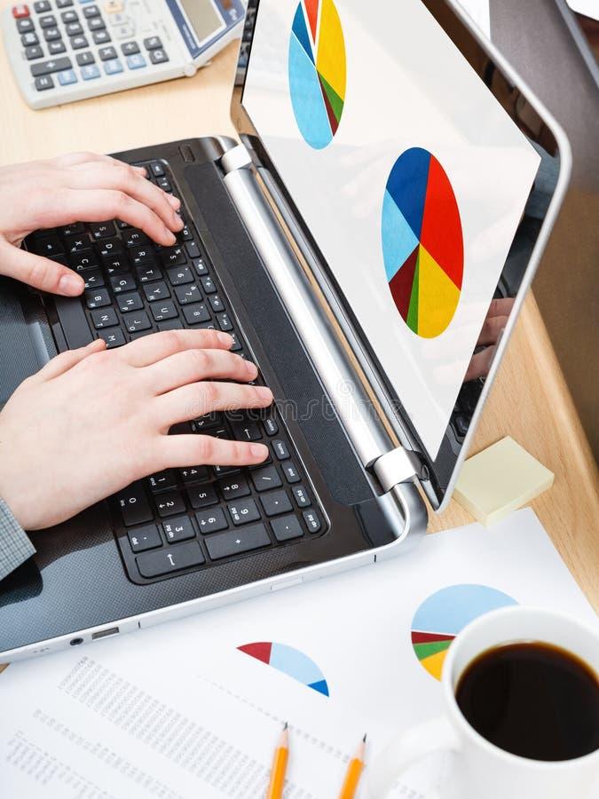 L'impiegato di concetto funziona con il computer portatile ed il grafico sullo schermo fotografie stock libere da diritti