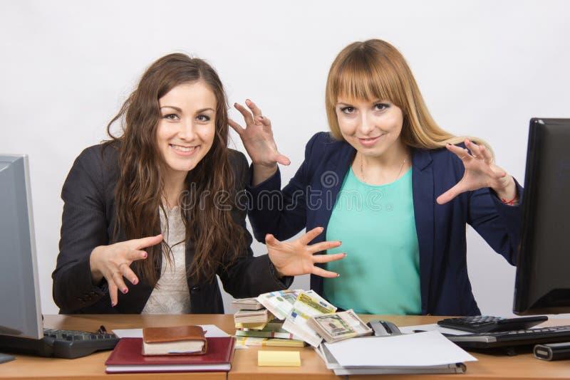 L'impiegato di ufficio due felice ed allegro si è chinato un mucchio di soldi fotografia stock