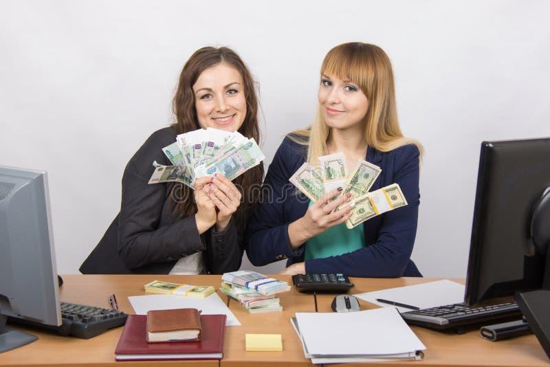 L'impiegato di ufficio felice due ad una tavola che tiene un fan di soldi imballa fotografie stock