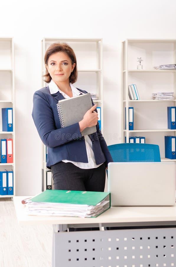 L'impiegato femminile di mezza età che si siede all'ufficio immagine stock