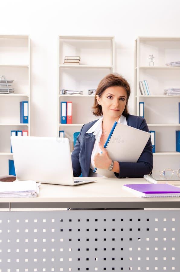 L'impiegato femminile di mezza età che si siede all'ufficio fotografia stock