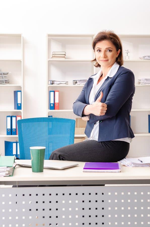 L'impiegato femminile di mezza età che si siede all'ufficio immagini stock