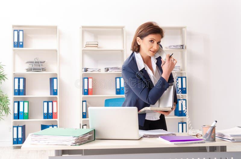 L'impiegato femminile di mezza età che si siede all'ufficio fotografia stock libera da diritti