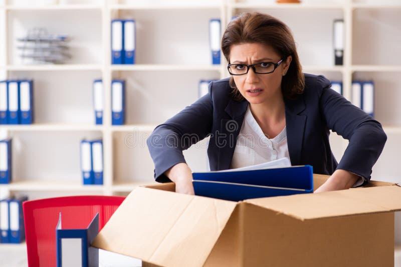 L'impiegato femminile di mezza et? che ? infornato dal suo lavoro fotografie stock