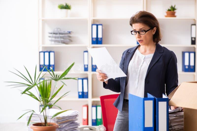 L'impiegato femminile di mezza et? che ? infornato dal suo lavoro immagini stock libere da diritti