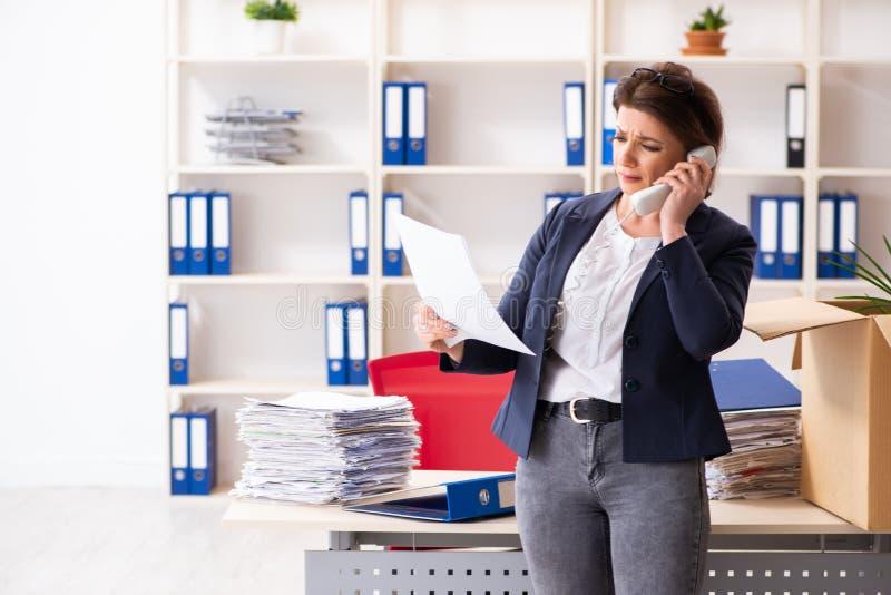 L'impiegato femminile di mezza et? che ? infornato dal suo lavoro immagine stock
