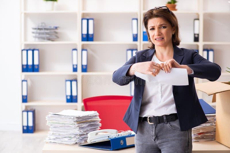 L'impiegato femminile di mezza et? che ? infornato dal suo lavoro fotografie stock libere da diritti