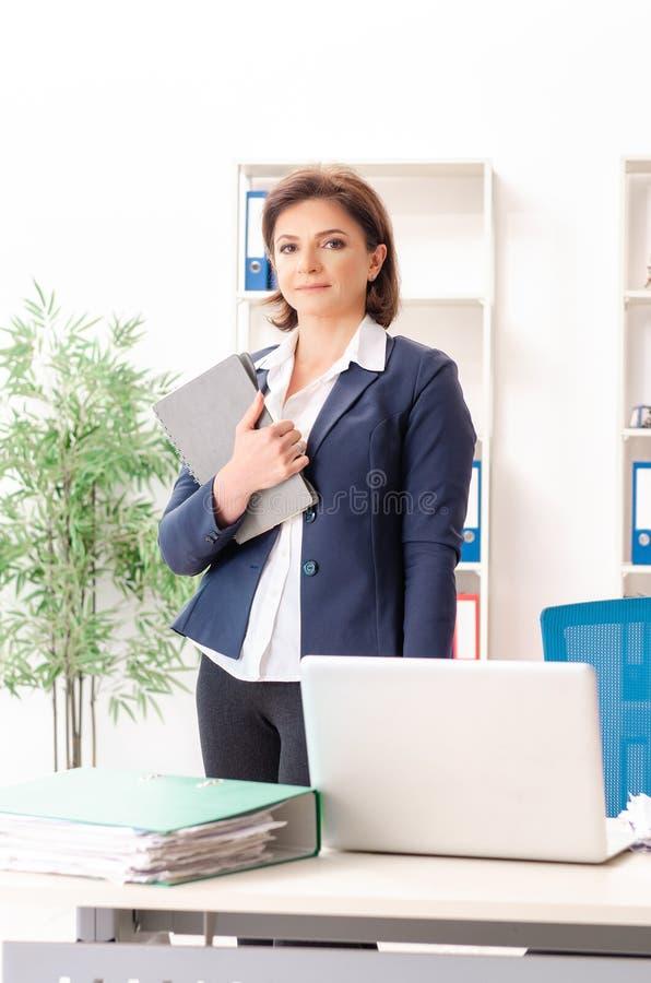 L'impiegato femminile di mezza et? che si siede all'ufficio immagine stock libera da diritti
