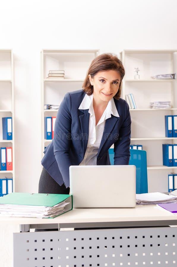 L'impiegato femminile di mezza et? che si siede all'ufficio fotografia stock libera da diritti