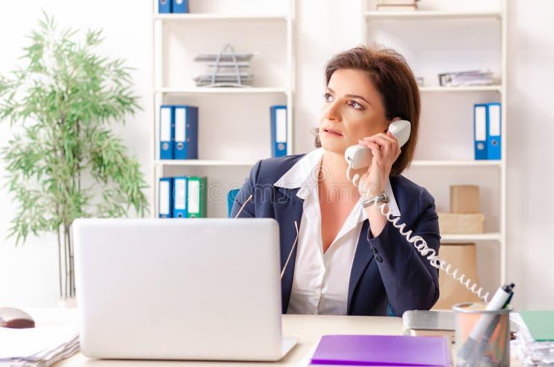 L'impiegato femminile di mezza et? che si siede all'ufficio fotografie stock