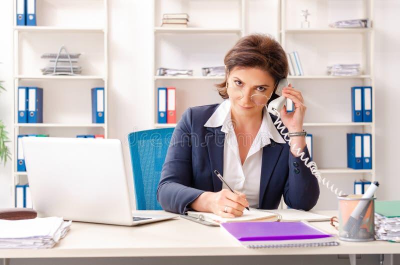 L'impiegato femminile di mezza et? che si siede all'ufficio immagine stock