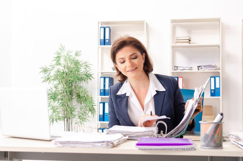L'impiegato femminile di mezza et? che si siede all'ufficio immagini stock libere da diritti