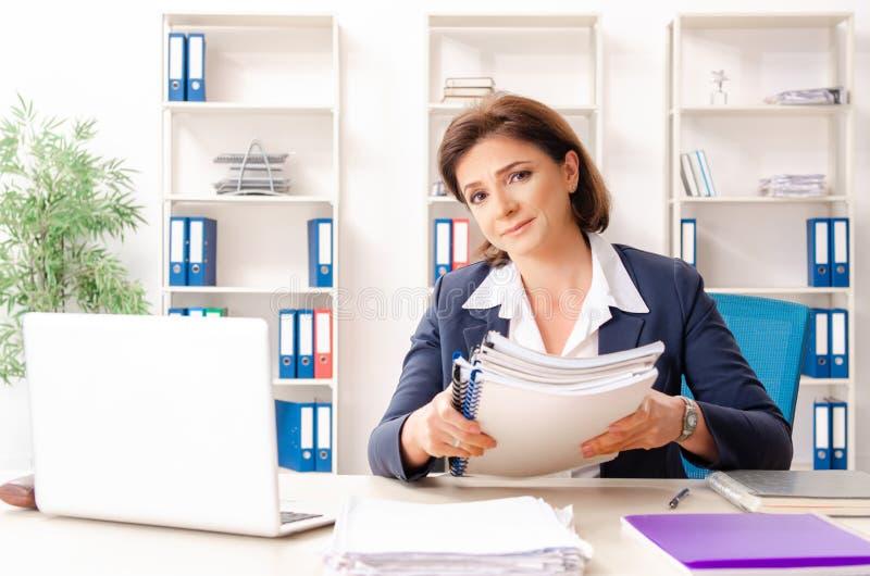 L'impiegato femminile di mezza et? che si siede all'ufficio immagini stock