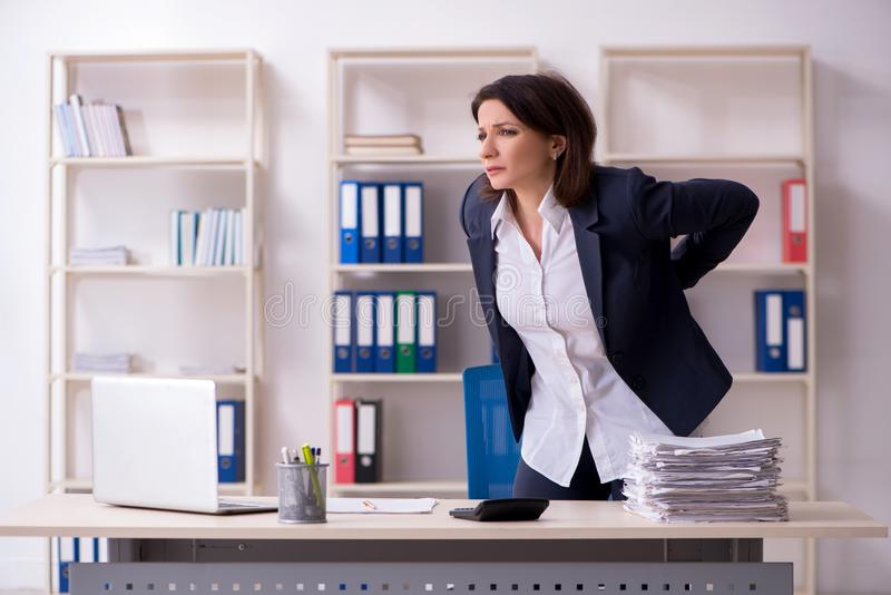 L'impiegato femminile di mezza et? che soffre nell'ufficio fotografia stock
