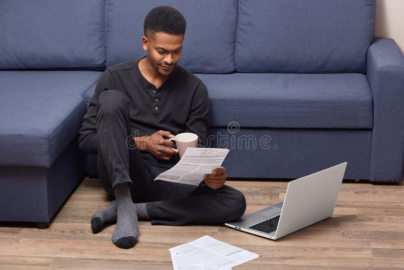 L'imprenditore afroamericano indignato osserva con l'espressione dispiaciuta i documenti cartacei, porta la tazza di caffè elimin fotografia stock libera da diritti