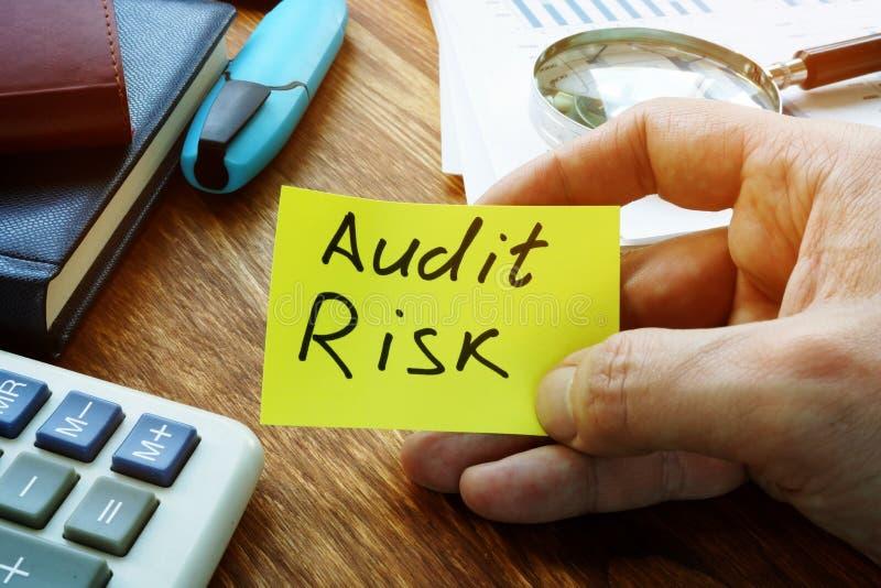 L'imprenditore possiede un segno di rischio di audit su un foglio immagine stock libera da diritti