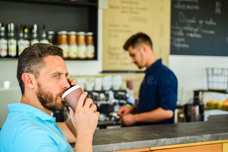 L'imprenditore sicuro sceglie la bevanda in tazza di carta per andare mentre comunichi il cellulare Salvi il vostro tempo L'uomo  fotografia stock libera da diritti
