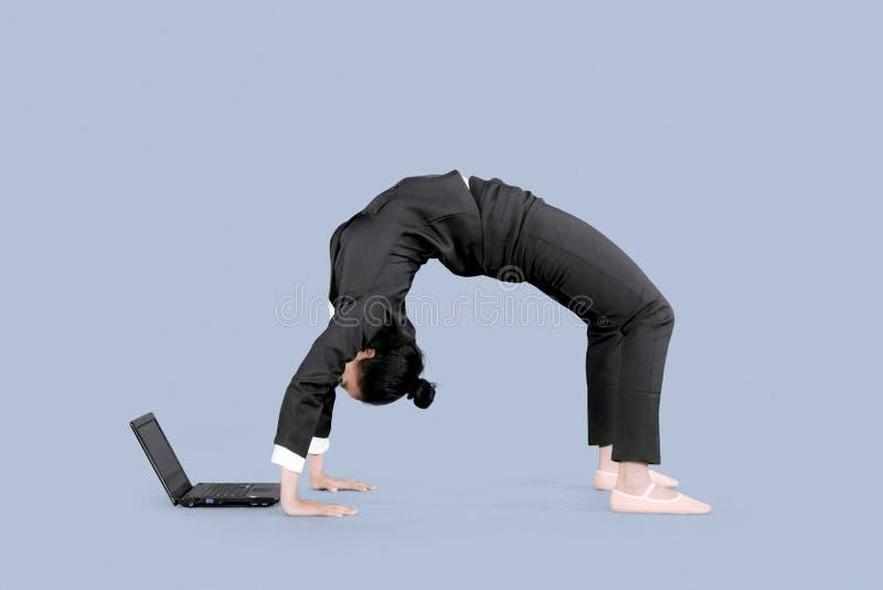 L'imprenditore utilizza un computer portatile con la posa posteriore della curvatura fotografia stock libera da diritti