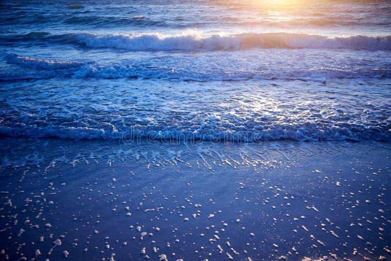 L'incandescenza del tramonto dorata sopra delicatamente l'avvolgimento ondeggia immagini stock libere da diritti