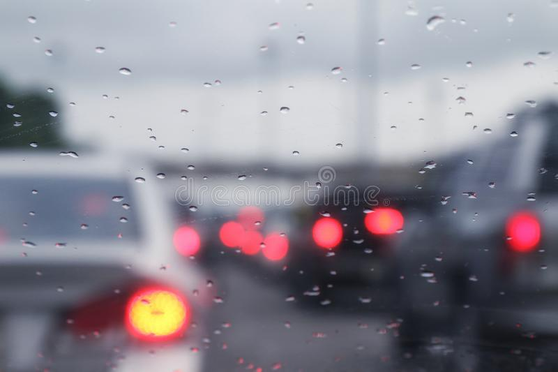 L'inceppamento e le gocce di pioggia vaghi dell'automobile di traffico del fondo innaffiano su vetro con l'automobile di illumina fotografia stock