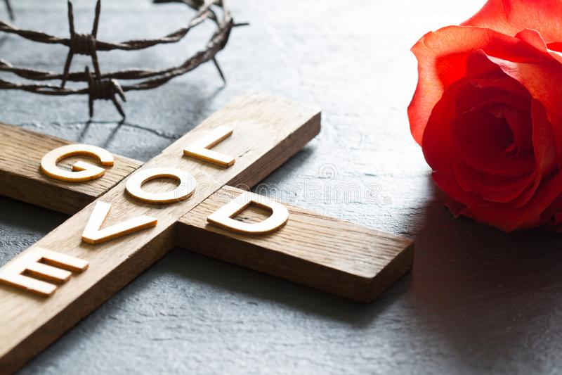 L'incrocio di legno cristiano di Pasqua con un dio dell'iscrizione è fondo di religione dell'estratto della rosa rossa e di amore immagine stock libera da diritti