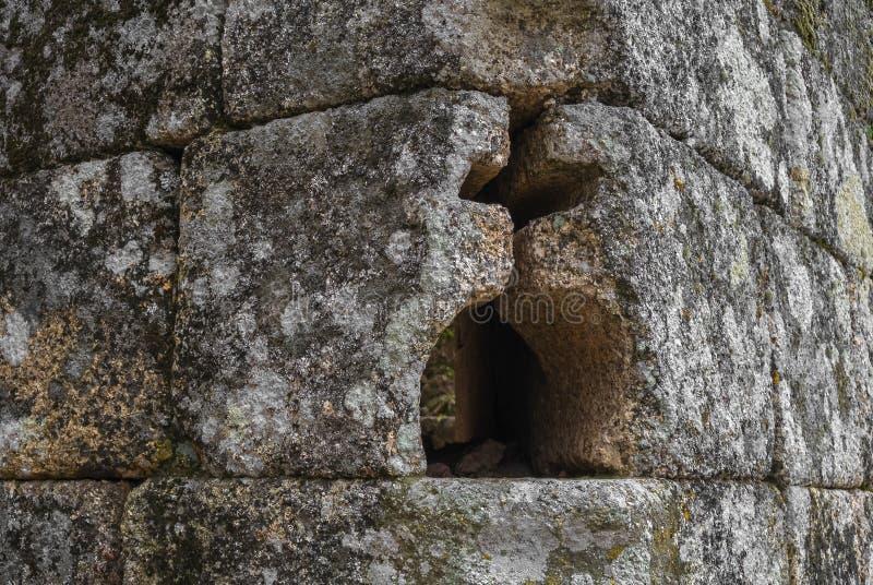 L'incrocio ed il globo cristiani hanno modellato il foro nella parete di pietra fotografie stock