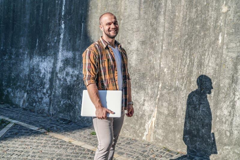 L'indépendant barbu audacieux bel se tenant dehors contre le mur gris de grenier avec son ordinateur portable et écoute la musiqu photos libres de droits
