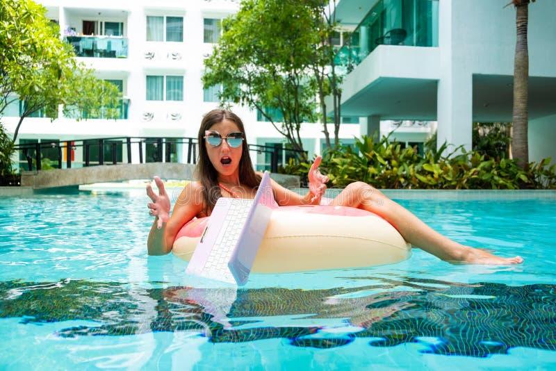 L'indépendant féminin s'assied en cercle gonflable dans la piscine et laisse tomber l'ordinateur portable dans l'eau Occupé penda images stock