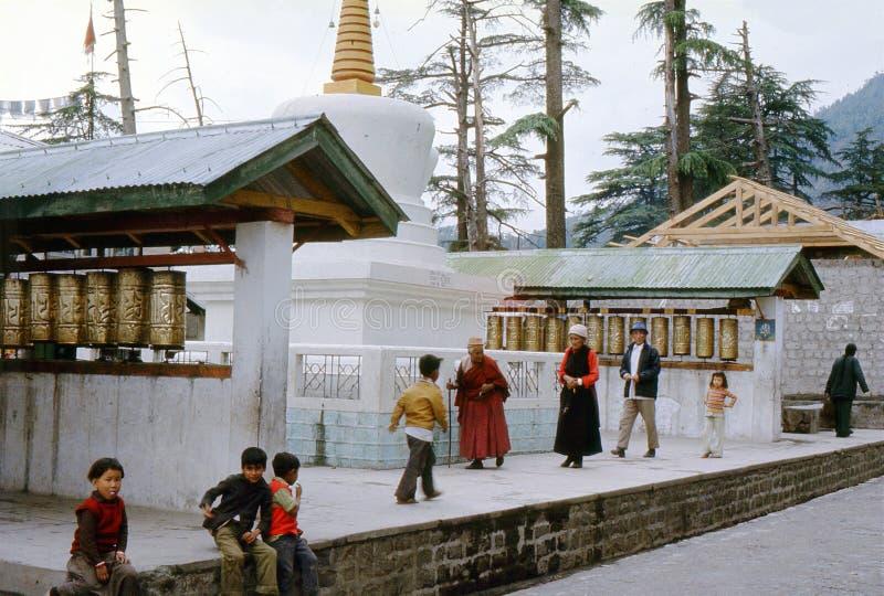 1977 l'Inde Pèlerins et enfants tibétains par les moulins de prière image stock