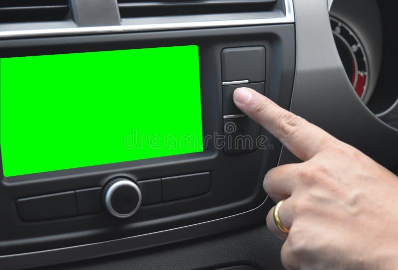 L'index asiatique d'homme presse un bouton sur le contrôle moderne d'automobile de tableau de bord de voiture et l'écran vert ave photo libre de droits