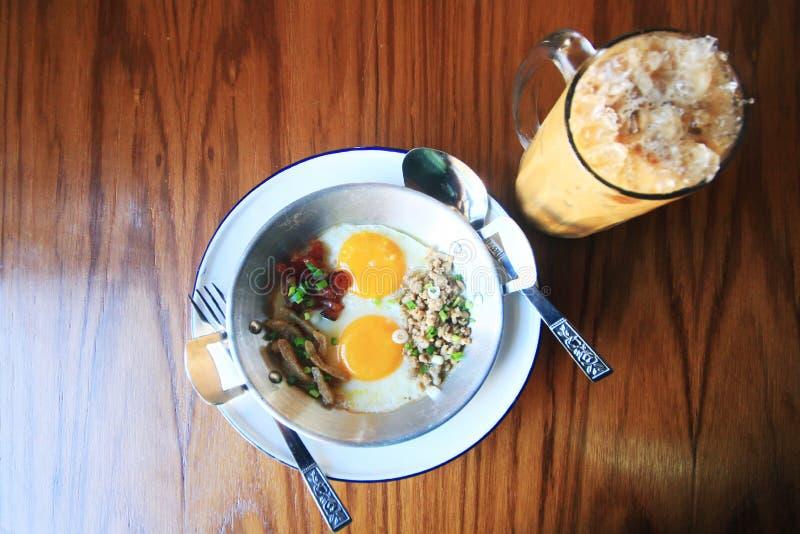 L'Indocina ha saltato in padella l'uovo con le guarnizioni nello stile tailandese casalingo con il caffè di ghiaccio immagini stock