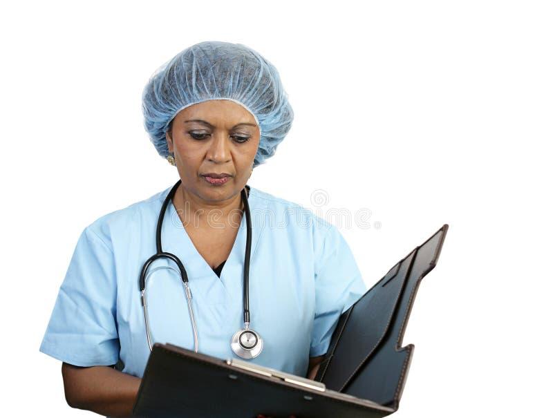 L'infermiera chirurgica esamina il diagramma fotografia stock