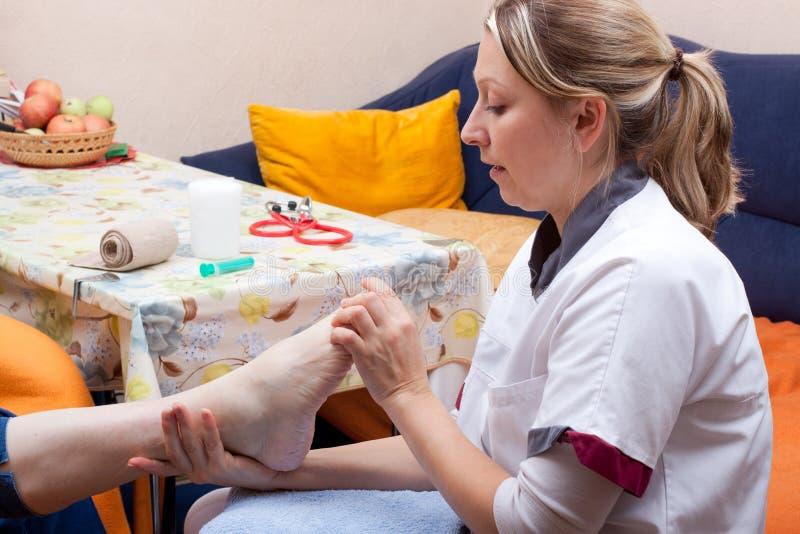 L'infermiera esamina il piede di un paziente immagine stock libera da diritti