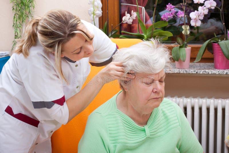 L'infermiera massaggia la testa di un anziano fotografie stock libere da diritti