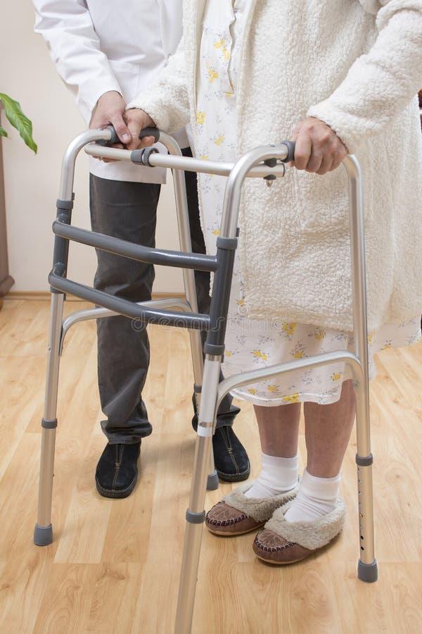 L'infermiere aiuta la donna anziana a camminare con il camminatore di riabilitazione fotografie stock libere da diritti