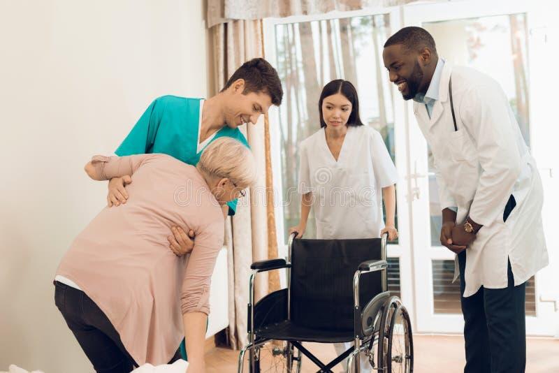 L'infermiere aiuta una donna anziana ad uscire del letto ed ad entrare in una sedia a rotelle fotografia stock