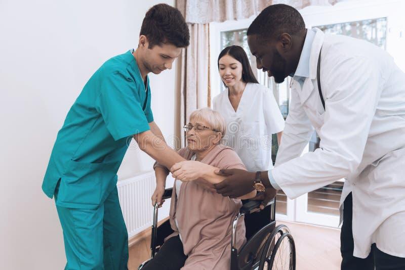 L'infermiere aiuta una donna anziana ad uscire del letto ed ad entrare in una sedia a rotelle fotografia stock libera da diritti