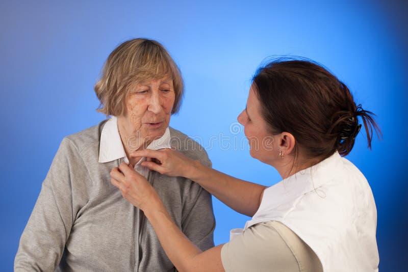 L'infermiere aiuta una donna senior con vestirsi fotografia stock
