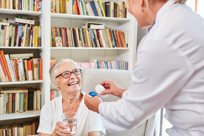 L'infermiere dà la sua droga ad un anziano fotografia stock