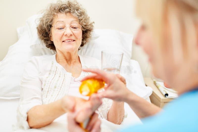 L'infermiere dà le pillole senior della donna fotografia stock libera da diritti